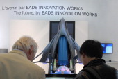Visitors looks at the model of a future commercial high speed transport system called ZEHST at the European plane manufacturer EADS stand at the...