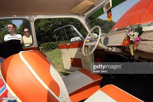 Visitors looks inside a 1963 Trabant P60 automobile at a Trabant enthusiasts' weekend on August 8 2015 near Nossen Germany The Trabant also called...