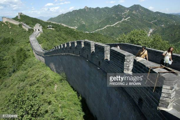 Visitors make their way along a restored section of the Great Wall at Badaling in the mountains north of Beijing 29 August 2004 China's Great Wall is...