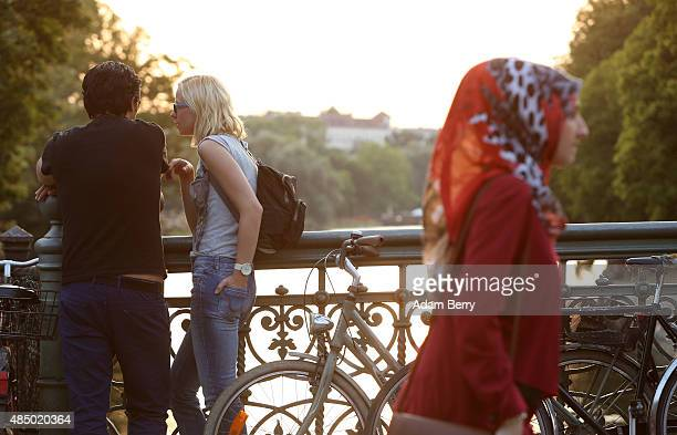 Visitors mingle along the Landwehrkanal in the Kreuzberg district of the city on August 23 2015 in Berlin Germany Rainy weather is expected early in...