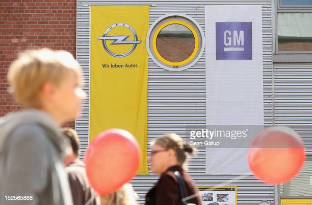 Visitors mostly Opel employees former employees and their family members walk past company logos at the Opel Insignia and Astra factory during a...