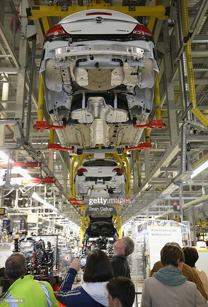 Visitors mostly Opel employees former employees and their family members walk past the assembly line of the Opel Insignia during a celebration...