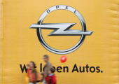 Visitors mostly Opel employees former employees and their family members walk past the Opel company logo at the Opel Insignia and Astra factory...