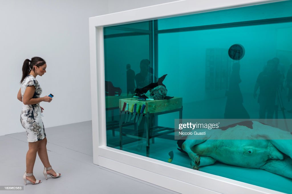 Visitors observe Damien Hirst's artworks at the Relics Exhibition by Damien Hirst at Al Riwaq space next to Doha's Museum of Islamic Art on October 9, 2013 in Doha, Qatar.