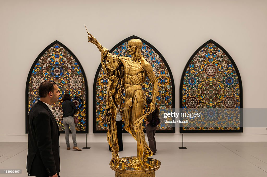 Visitors observe Damien Hirst's 'Saint Bartholomew, Exquisite Pain' artwork at the Relics Exhibition by Damien Hirst at Al Riwaq space next to Doha's Museum of Islamic Art on October 9, 2013 in Doha, Qatar.