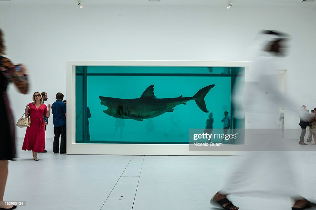 Visitors observe Damien Hirst's 'The immortal' at the Relics Exhibition by Damien Hirst at Al Riwaq space next to Doha's Museum of Islamic Art on October 9, 2013 in Doha, Qatar