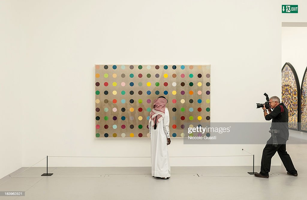 Visitors observe one of Damien Hirst's spot painting works of art at the Relics Exhibition by Damien Hirst at Al Riwaq space next to Doha's Museum of Islamic Art on October 9, 2013 in Doha, Qatar.