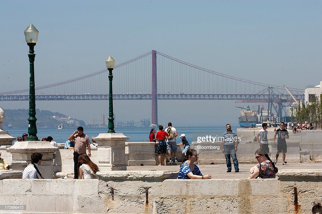 Visitors observer the view across the Tejo river towards the 25th of April bridge in Lisbon, Portugal, on Wednesday, July 3, 2013. Portuguese borrowing costs topped 8 percent for the first time this year after two ministers quit, signaling the government will struggle to implement further budget cuts as its bailout program enters its final 12 months. Photographer: Mario Proenca/Bloomberg via Getty Images