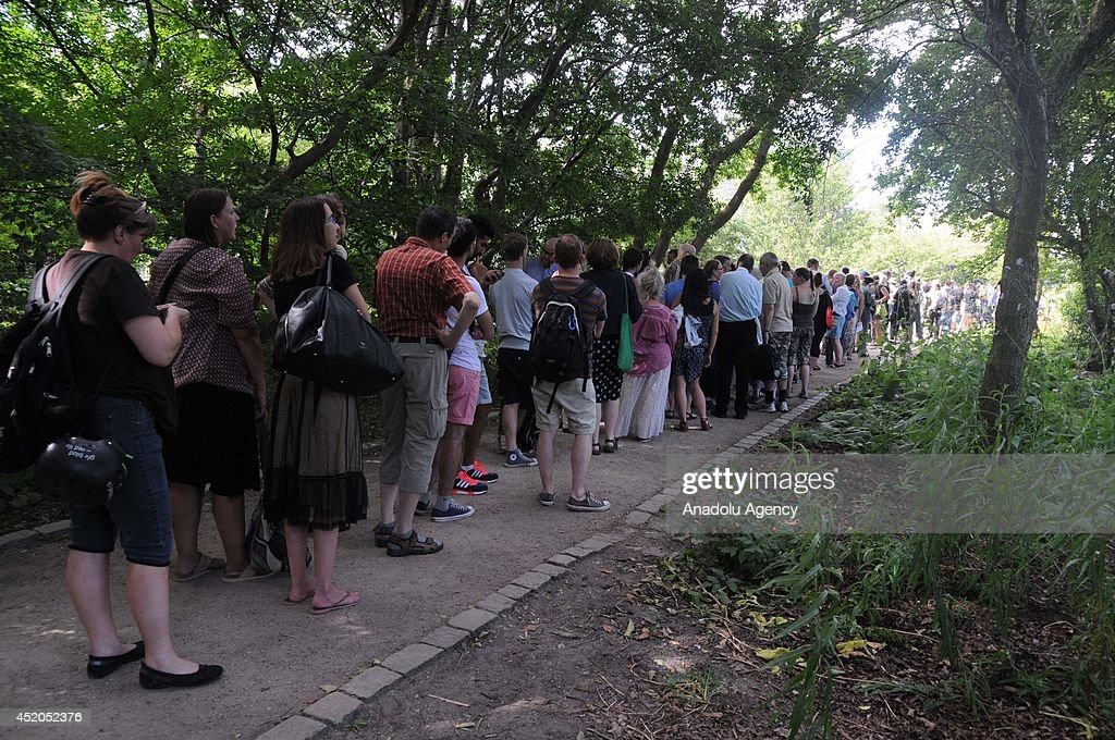 Visitors of Copenhagen Botanic Garden line up to watch a rare blooming of the Titan Arum in Copenhagen, Denmark on July 9, 2014. The titan Arum also known as Corpse Flower produces one of the largest flowering structures and one of the foulest odors in the plant kingdom. With its huge flowering structure rising up to three meters above the ground, and its single immense leaf, it certainly is a giant among plants, as its name suggests. It blooms only a few times in its 40-year life span, and the bloom lasts for two and a half days at the most.