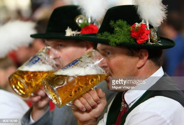 Visitors of the 176th Oktoberfest beer festival drink a mug of beer on September 20 2009 in Munich Germany Oktoberfest is Germany's and the world...