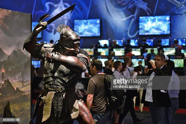 Visitors of the 'Gamescom' fair play the 'Final Fantasy' computer game on August 13 2014 in Cologne western Germany The trade fair for interactive...