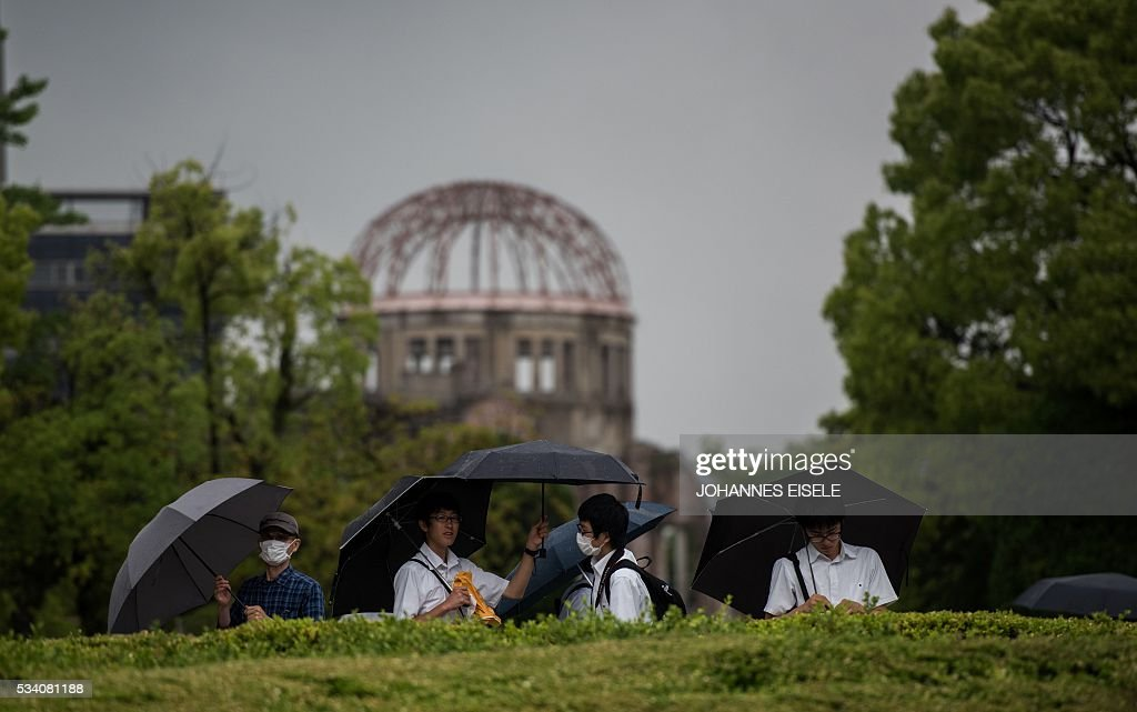 Visitors of the Hiroshima Peace Memorial park stand in front of the Peace Memorial Genbaku Dome in Naka Ward, Hiroshima Prefecture on May 25, 2016. Barack Obama is set to become the first sitting US president to visit Hiroshima when he journeys on May 27 with Japanese Prime Minister Shinzo Abe, hallowed ground to Japanese but, for more than 70 years, a no-go zone for 11 of his Oval Office predecessors. / AFP / JOHANNES