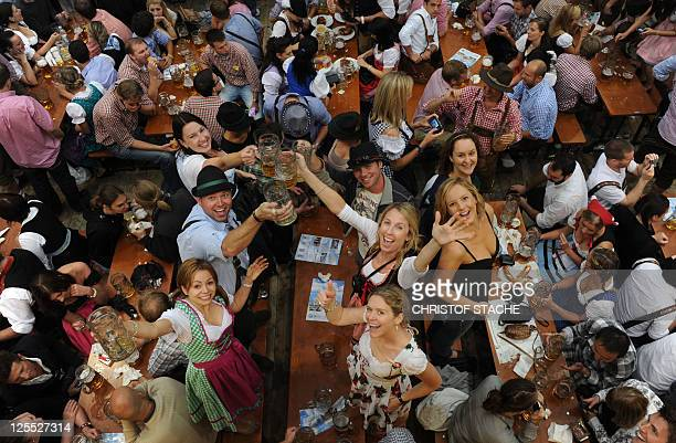 Visitors of the Oktoberfest beer festival celebrate in a beer tent at the Theresienwiese fair grounds in Munich southern Germany on September 18 2011...