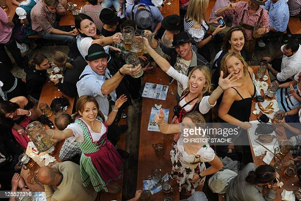 CROP Visitors of the Oktoberfest beer festival celebrate in a beer tent at the Theresienwiese fair grounds in Munich southern Germany on September 18...