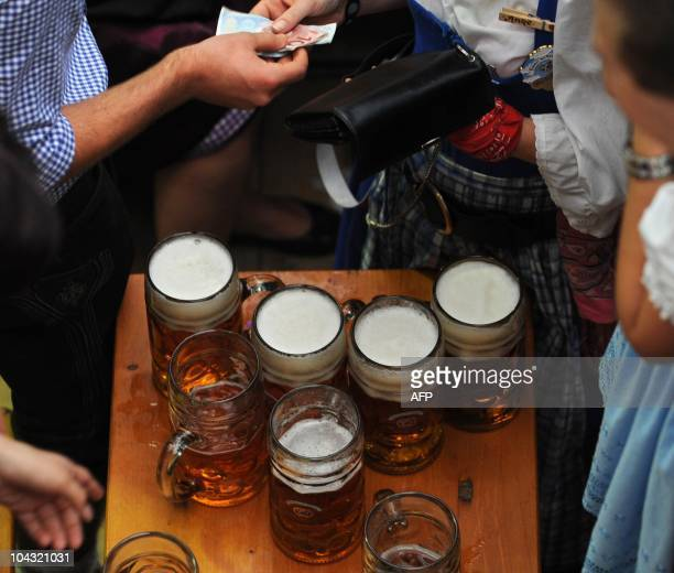 Visitors of the Oktoberfest beer festival pay their beer mugs in a tent at the Theresienwiese fairground in Munich southern Germany September 20 2010...