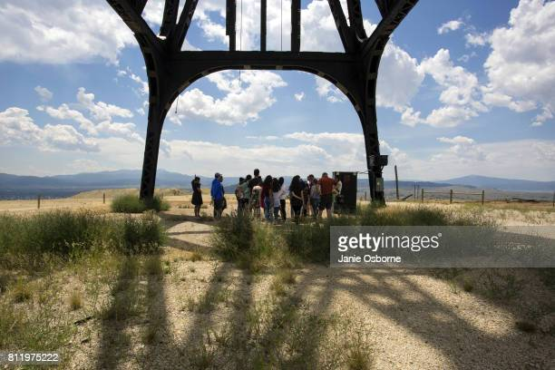 Visitors on a tour of the Berkeley Pit and surrounding area listen to the tour guide speak while standing under a gallows frame on July 6 2017 in...