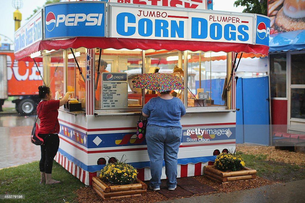 Visitors order snacks from a concession stand at the Iowa State Fair on August 6 2014 in Des Moines Iowa The fair opens to the public on August 7...