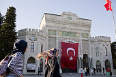 Visitors pass a large Turkish national flag at the entrance to Istanbul University in Istanbul Turkey on Tuesday July 19 2016 Moody's Investor...