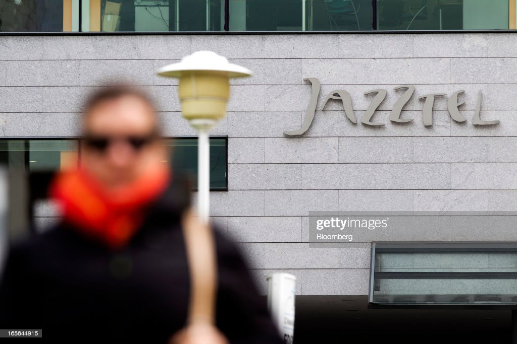Visitors pass a logo outside the offices of Jazztel Plc in Alcobendas, Spain, on Thursday, April 4, 2013. Jazztel almost doubled its share of the Spanish broadband market from 2009 to 2012 as it focused mostly on the fixed-telephone business through a reliable and affordable product that has gained popularity among debt-strapped Spaniards. Photographer: Angel Navarrete/Bloomberg via Getty Images