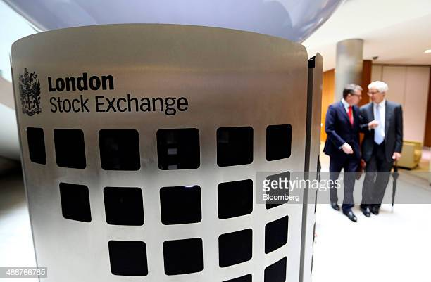 Visitors pass a London Stock Exchange sign inside the main atrium of the London Stock Exchange Group Plc's headquarters in London UK on Thursday May...