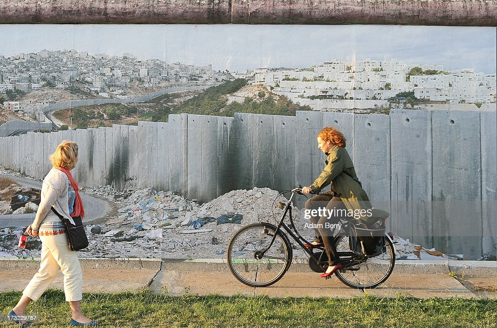 Visitors pass a photo of a separation wall in the Shu' Fat Refugee Camp in the Pisgat Ze'ev settlement in the West Bank, Occupied Palestinian Territories, in the 'Wall on Wall' exhibition at the East Side Gallery section of the former Berlin Wall on July 10, 2013 in Berlin, Germany. A series of photos shot since 2006 by photographer Kai Wiedenhoefer hanging on the Western, river Spree side of the Wall features large pictures of separation barriers in Baghdad, Korea, Cyprus, Mexico, Morocco, Israel, Belfast, and in the former East Germany itself. The opposite side of the stretch of the original Wall is known as East Side Gallery, a memorial to peace and freedom covered in murals questioning the legacy of the original Wall, and the subject of several demonstrations earlier in March this year when sections of it were threatened with removal to make way for a construction site for luxury apartment buildings, discussion of which is still ongoing with a decision expected to be reached in early August.