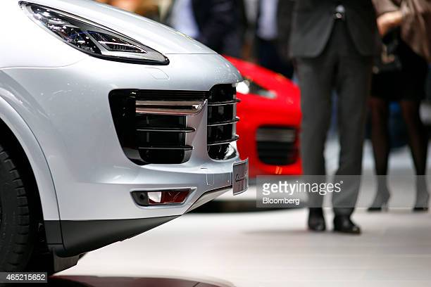 Visitors pass a Porsche Cayenne SUV luxury automobile produced by Porsche SE as it stands on display on day two of the 85th Geneva International...