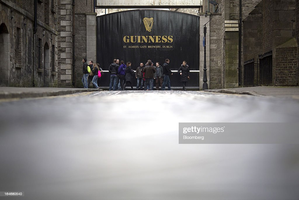 Visitors pass an entrance to the Guinness St. James's Gate Brewery, a brand of Diageo Plc, in Dublin, Ireland, on Saturday, March 16, 2013. Ireland's renewed competiveness makes it a beacon for the U.S. companies such as EBay, Google Inc. and Facebook Inc., which have expanded their operations in the country over the past two years. Photographer: Simon Dawson/Bloomberg via Getty Images