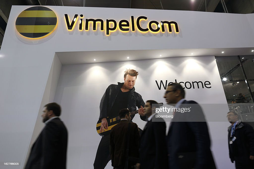 Visitors pass an illuminated logo above the VimpelCom Ltd. pavilion at the Mobile World Congress in Barcelona, Spain, on Tuesday, Feb. 26, 2013. The Mobile World Congress, where 1,500 exhibitors converge to discuss the future of wireless communication, is a global showcase for the mobile technology industry and runs from Feb. 25 through Feb. 28. Photographer: Simon Dawson/Bloomberg via Getty Images