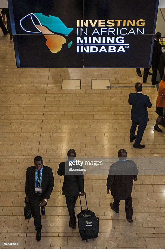 Visitors pass beneath a banner on the opening day of the Investing in African Mining Indaba in Cape Town, South Africa, on Monday, Feb. 8, 2016. With many miners battling to stay afloat, fewer are willing to shell out 1,140 pounds ($1,641) for the Investing in African Mining Indaba conference in South Africa and business-class airfare. Photographer: Waldo Swiegers/Bloomberg via Getty Images