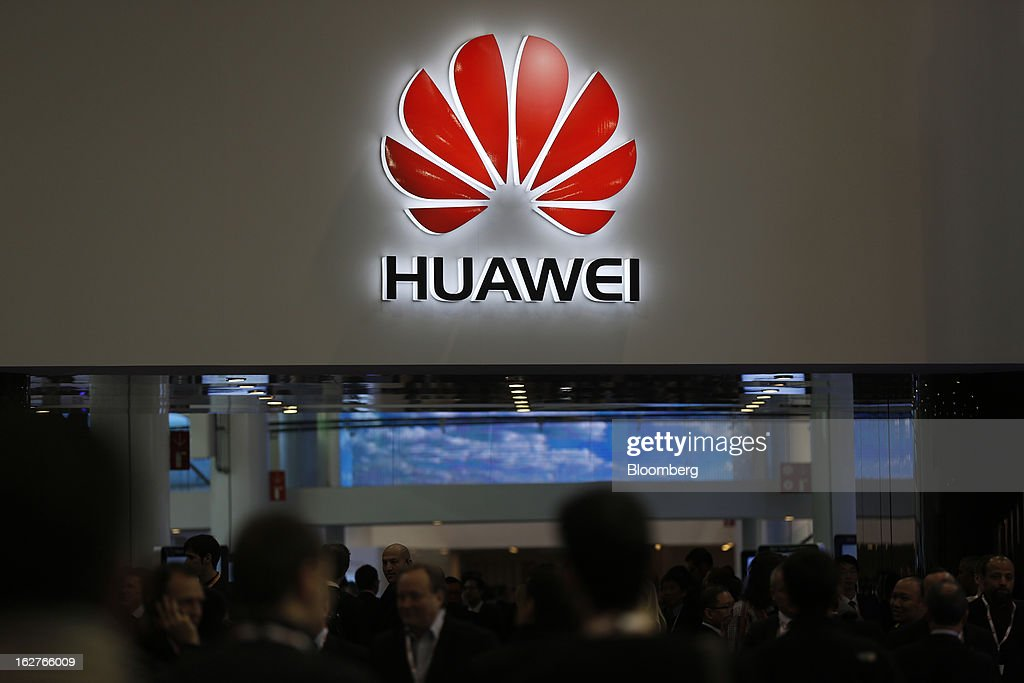 Visitors pass beneath an illuminated Huawei Technologies Co. sign near the company's pavilion at the Mobile World Congress in Barcelona, Spain, on Tuesday, Feb. 26, 2013. The Mobile World Congress, where 1,500 exhibitors converge to discuss the future of wireless communication, is a global showcase for the mobile technology industry and runs from Feb. 25 through Feb. 28. Photographer: Simon Dawson/Bloomberg via Getty Images