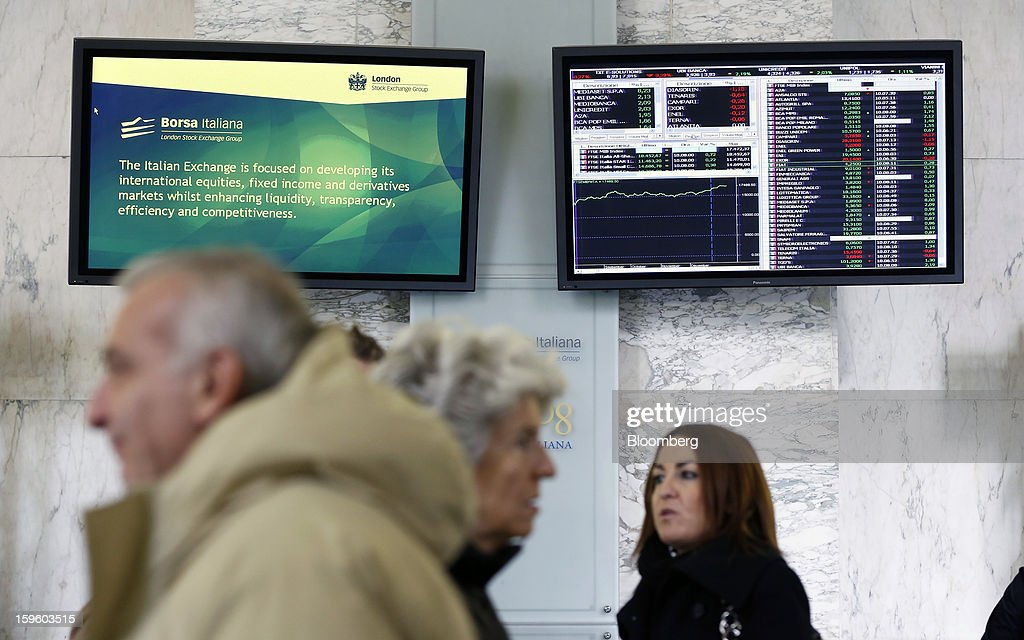 Visitors pass beneath electronic display boards inside the Borsa Italiana, Italy's stock exchange, which is part of the London Stock Exchange Group Plc, in Milan, Italy, on Thursday, Jan. 17, 2013. The euro-area economy won't return to growth until the next quarter as a recovery in Italy is delayed and France continues to shrink, according to a survey of economists. Photographer: Alessia Pierdomenico/Bloomberg via Getty Images