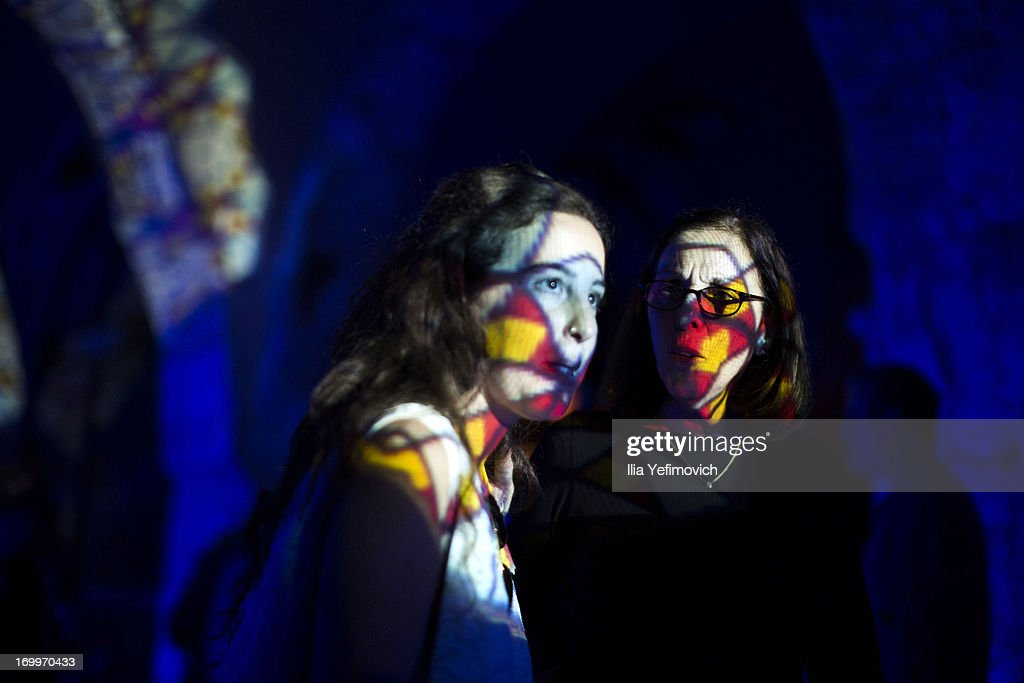 Visitors pass by a light installation during the annual Jerusalem Festival of Light on June 5, 2013 in Jerusalem, Israel. During the festival light installations are projected onto the historic buildings of Jerusalem's Old City.