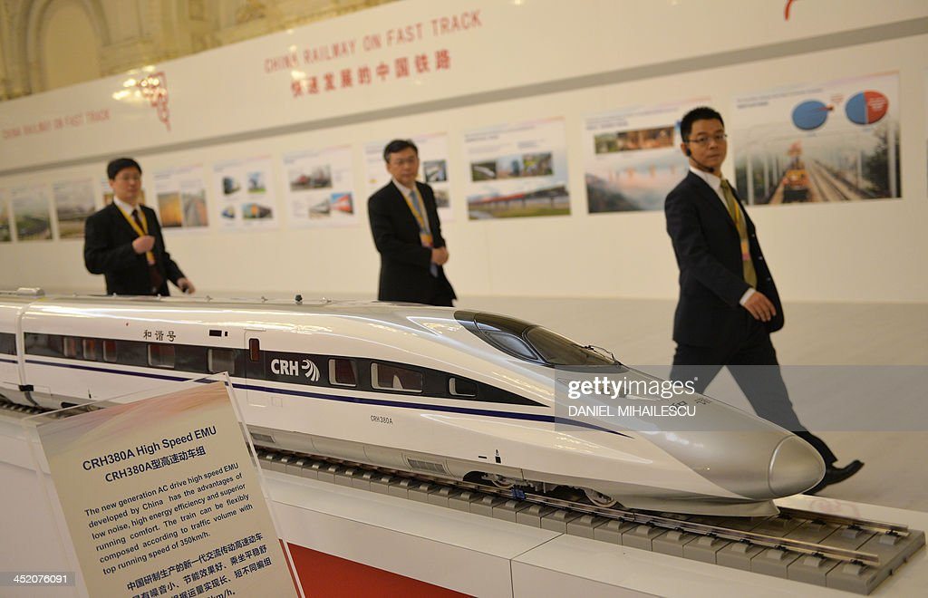 Visitors pass by a model of the Chinese fast train called CRH380A high speed EMU exhibited at the 'Meeting of Heads of Government of Central and Eastern European Countries and China' at the Parliament palace in Bucharest November 26, 2013.