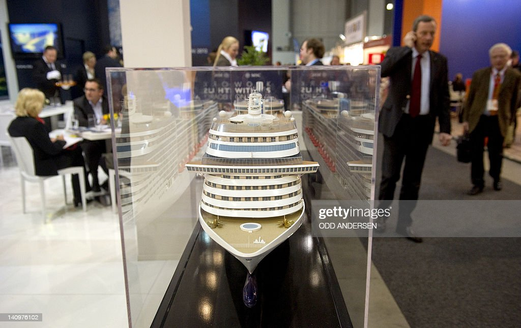 Visitors pass by the model of a cruise ship at the a cruising company booth at the ITB international tourism fair in Berlin on March 9, 2012. The ITB travel trade show, with 10,644 exhibitors from 187 countries, is due to run until March 11.