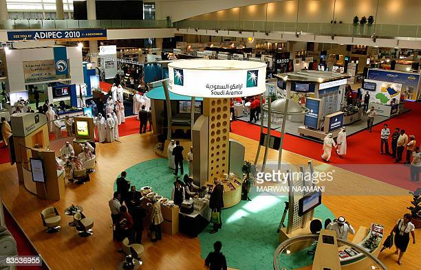 Visitors pass by the stand of Saudi Arabia's national oil company Aramco at the Abu Dhabi International Petroleum Exhibition and Conference in Abu...