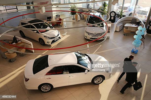 Visitors pass display models of Toyota's Venza right and Verso left vehicles in the showroom of a Toyota Motor Corp automobile dealership in Moscow...