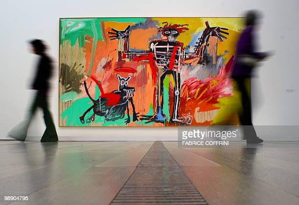 Visitors pass in front of a painting by JeanMichel Basquiat intitled 'Boy and Dog in a Johnnypump' on May 7 2010 in Basel The Beyeler Foundation...
