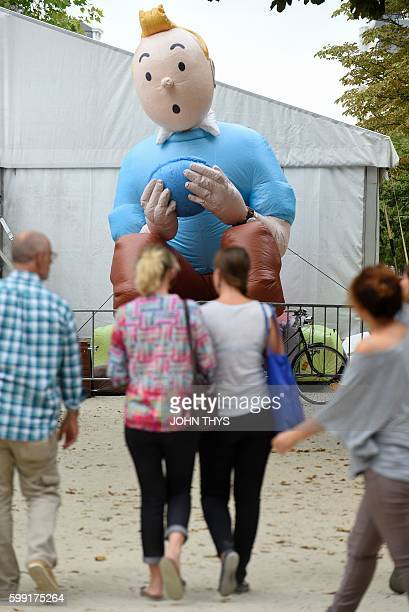 Visitors pass in front of an inflatable of Belgian comics series character Tintin during the festival 'Fete de la BD' in Brussels on September 2 2016...