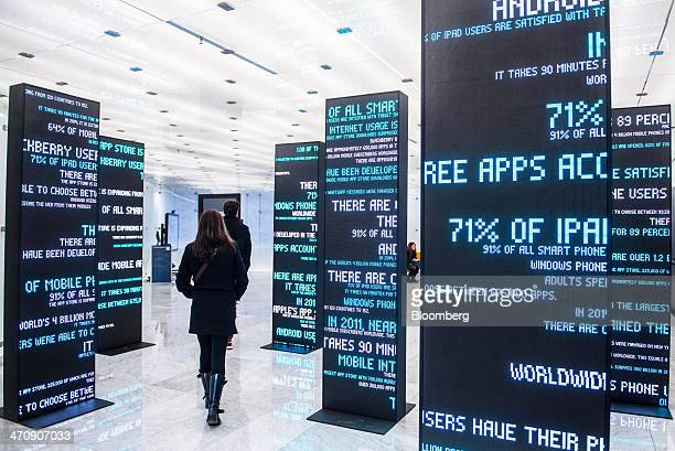 Visitors pass mobile technology information panels at the Mobile World Center an exhibition and innovation space in Barcelona Spain on Thursday Feb...