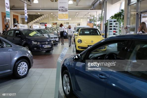 Visitors pass new VW vehicles for sale inside an automobile showroom operated by Volkswagen AG in Moscow Russia on Friday March 28 2014 Foreign...