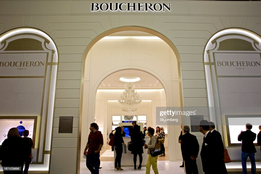 Visitors pass the Boucheron booth, a unit of PPR SA, during the Baselworld watch fair in Basel, Switzerland, on Thursday, April 25, 2013. The annual fair attracts 2,000 companies from the watch, jewelry and gem industries to show their new wares to more than 100,000 visitors. Photographer: Gianluca Colla/Bloomberg via Getty Images