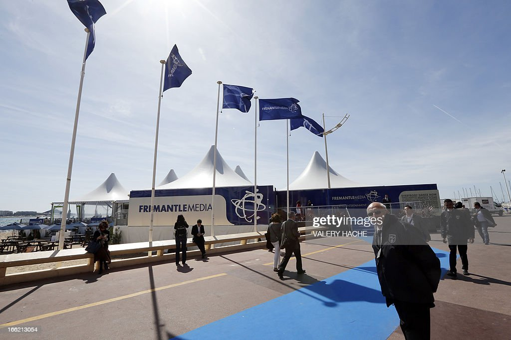 Visitors pass the 'Fremantle Media' stand, on April 10, 2013 in Cannes, southeastern France, during the MIPTV, one of the world's largest broadcasting and audio-visual trade show.