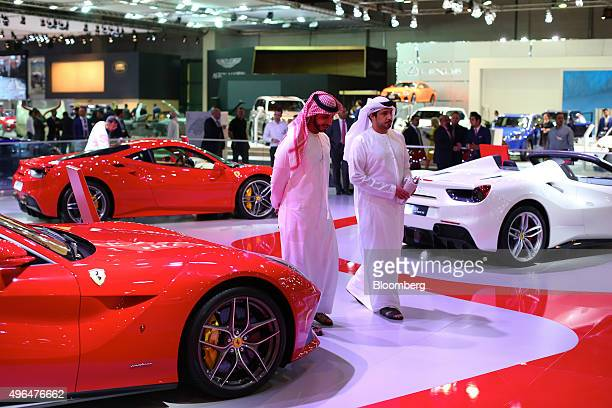 Visitors pass the latest Ferrari 488 GTB supercars right manufactured by Ferrari SpA during the Dubai Motor Show at the World Trade Center in Dubai...