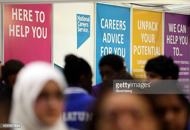 Visitors pass the National Careers Service job exhibition booth during the Skills London job fair in London UK on Friday Nov 21 2014 UK unemployment...