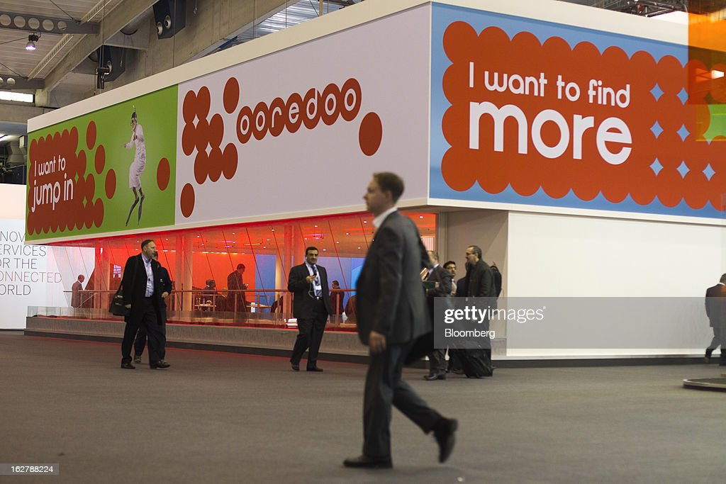 Visitors pass the Ooredoo pavilion, operated by Qtel Group, at the Mobile World Congress in Barcelona, Spain, on Tuesday, Feb. 26, 2013. The Mobile World Congress, where 1,500 exhibitors converge to discuss the future of wireless communication, is a global showcase for the mobile technology industry and runs from Feb. 25 through Feb. 28. Photographer: Angel Navarrete/Bloomberg via Getty Images