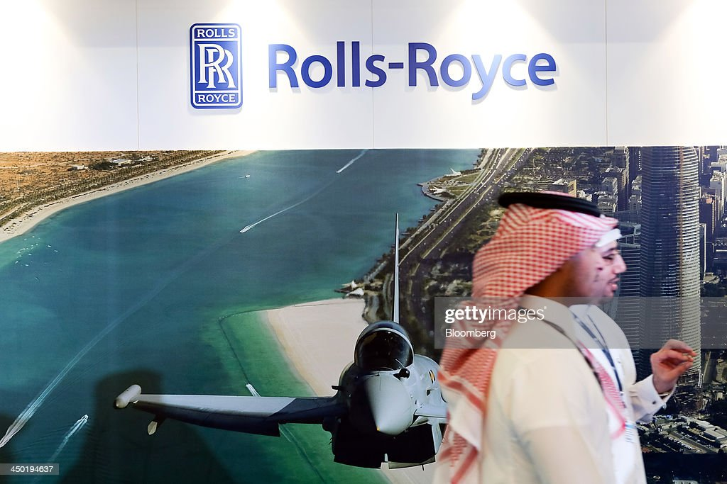 Visitors pass the Rolls-Royce Holdings Plc., stand and a photograph of the Eurofighter Typhoon aircraft, manufactured by BAE Systems Plc., on display in the exhibition halls during the 13th Dubai Airshow at Dubai World Central (DWC) in Dubai, United Arab Emirates, on Sunday, Nov. 17, 2013. The 13th edition of the biennial 2013 Dubai Airshow, the Middle East's leading aerospace event organized by F&E Aerospace. Photographer: Duncan Chard/Bloomberg via Getty Images