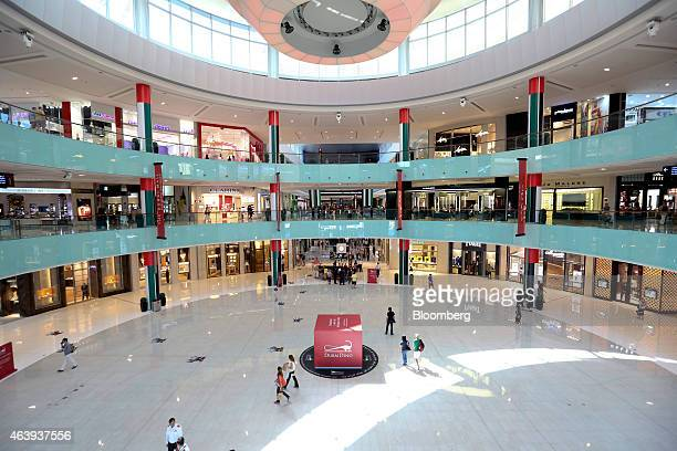 Visitors pass through a large atrium surrounded by luxury stores in the Dubai Mall operated by Emaar Malls Group in Dubai United Arab Emirates on...