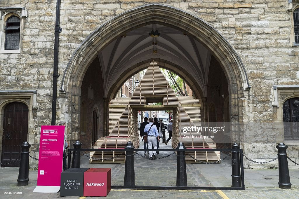 Visitors pass through the sculpture made from wooden flooring named 'Hakfolly' at the Clerkenwell Design Week in London, United Kingdom on May 24, 2016