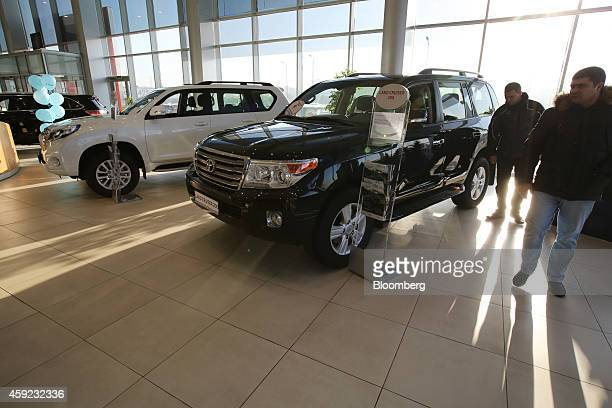 Visitors pass two different models of the Toyota Land Cruiser wagon a 200 right and a Prado in the showroom of a Toyota Motor Corp automobile...