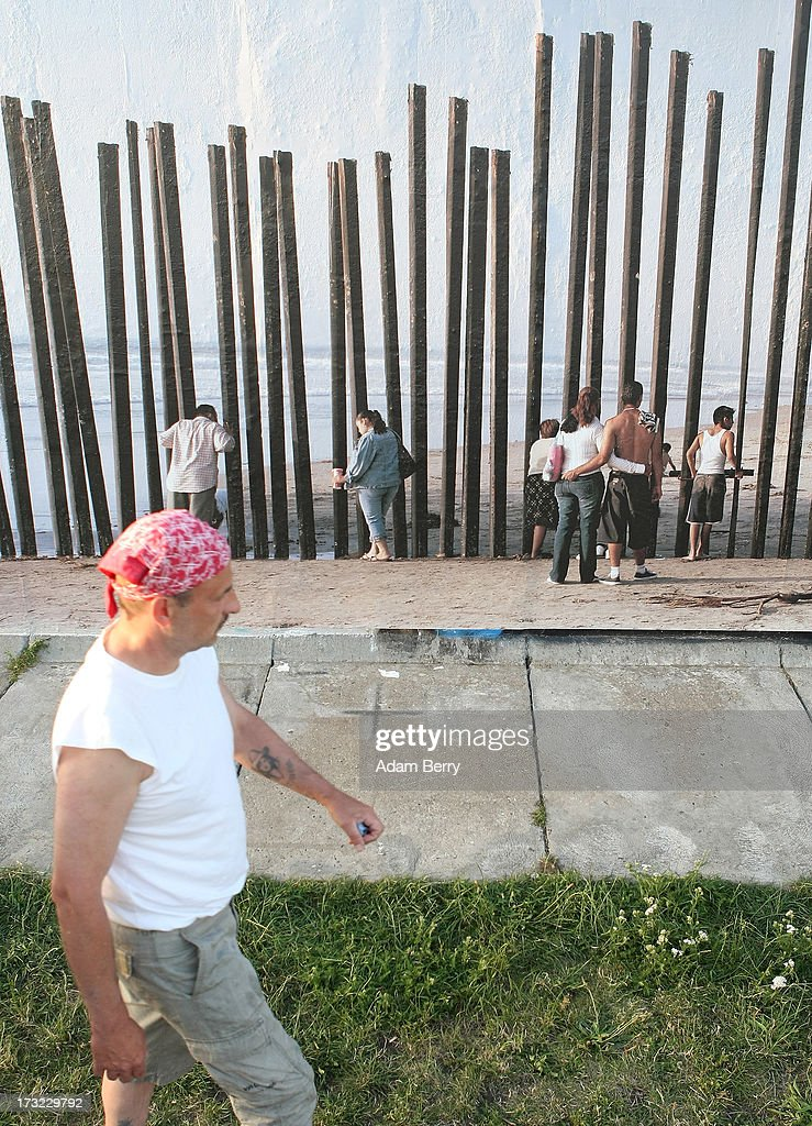 A visitors passes in front of a photo of the United States-Mexico border in Tijuana, Mexico, as it hangs as part of the 'Wall on Wall' exhibition at the East Side Gallery section of the former Berlin Wall on July 10, 2013 in Berlin, Germany. A series of photos shot since 2006 by photographer Kai Wiedenhoefer hanging on the Western, river Spree side of the Wall features large pictures of separation barriers in Baghdad, Korea, Cyprus, Mexico, Morocco, Israel, Belfast, and in the former East Germany itself. The opposite side of the stretch of the original Wall is known as East Side Gallery, a memorial to peace and freedom covered in murals questioning the legacy of the original Wall, and the subject of several demonstrations earlier in March this year when sections of it were threatened with removal to make way for a construction site for luxury apartment buildings, discussion of which is still ongoing with a decision expected to be reached in early August.